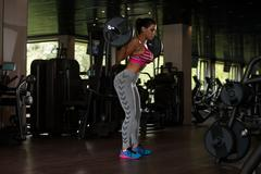 Mexican Woman Doing Exercise Barbell Squat - stock photo