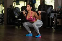 Latin Woman Doing Exercise Barbell Squat - stock photo