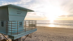 Time lapse of sunset over Pacific Ocean with lifeguard tower Stock Footage