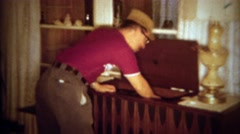 1966: Dad plays music chest vinyl record player for guest's listening pleasure.  Stock Footage