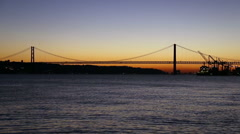Sunset view of The 25 de Abril Bridge in Lisbon, Portugal Stock Footage