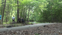 Roadside spectators watch rally car that passes by her through thick and gree Stock Footage
