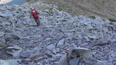 Tripper with ruxac in back climb a slope full of boulders Stock Footage