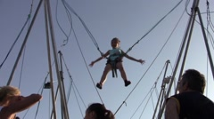 Child plays in a harness with elastic supervised by parents in an amusement p - stock footage