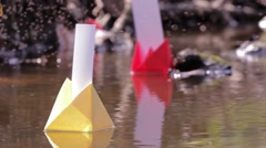 Colored paper boats drifted on a dirty water puddles Stock Footage