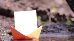 Orange paper ship floating near the shore tall river 95a Stock Footage