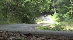 Motorcycles and off-road runs through dense forest and green on a paved road Stock Footage