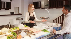 Seller helping customer choosing chilled fish in fishery Stock Footage