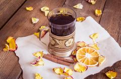 Cup of tea in coaster, dried oranges, dried rose petals on wooden background - stock photo