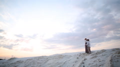Man and woman are kissing on sand quarry at sunset Stock Footage