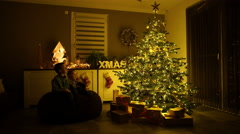 Two little boys at christmas tree in living room Stock Footage