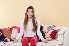 Helpless woman sitting on sofa in messy room home. Kuvituskuvat