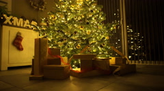 Illuminated christmas tree with presents at home Stock Footage