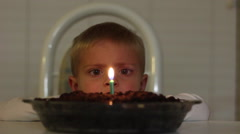 Boy Blowing Out Candle Stock Footage