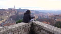 Lonely girl sitting on parapet, smokes and looks down upon the city Stock Footage