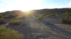 Aerial shot tracking low over desert floor toward mountains and sunset Stock Footage