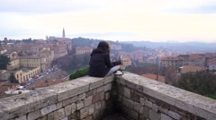 Lonely girl sitting on parapet, smokes and looks down upon the city 4K - stock footage