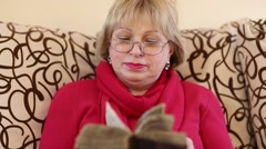 Senior woman sits on a divan and reads ancient book Stock Footage