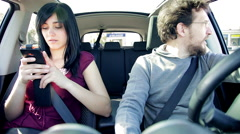 Man driving car unhappy about girlfriend chatting on cell phone Stock Footage