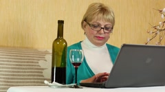 Woman with a bottle of wine sits at a table and communicates via laptop Stock Footage