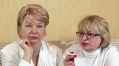 Two women sits on a couch and one woman smokes a cigarette Stock Footage