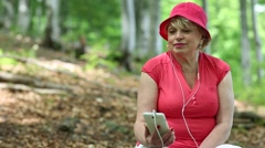Woman in red t-shirt and red cap in the forest listens to music - stock footage