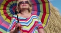 Blonde woman in sun glasses with many-coloured umbrella stands near haystack HD Footage