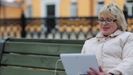 Stock Video Footage of Woman with Tablet PC sits on the bench and talks on Skype