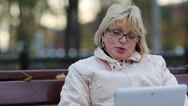 Stock Video Footage of Blonde woman with Tablet PC sits on the bench and talks on Skype