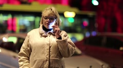 Woman talks on smartphone on the street Stock Footage