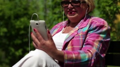 Woman with cigarette sits on the bench and communicates via smartphone Stock Footage
