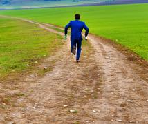 groom in blue suit running away with beer bottles on a field path - stock photo