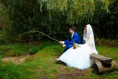 bride and groom fishing together - romantic wedding concept - stock photo