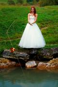 bride in dress with fishing rod sitting by a lake trying to catch a groom for - stock photo