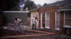1966: Home remodeling backyard workers shovel dirt digging leveling ground. - stock footage