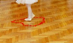 little bridesmaid girl legs in white dress on wedding dancefloor with rose - stock photo