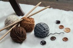 button and woolen yarn ball on carpet - stock photo