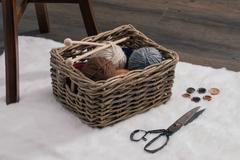scissors and yarn ball inside old basket on carpet - stock photo