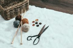 scissors, old basket and yarn ball on carpet - stock photo