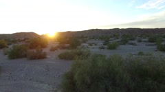 Aerial view moves towards mountains and sunset low over desert floor Stock Footage