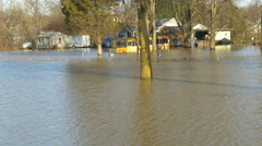 4K pan left to right of flooded area with cars, houses, school bus Stock Footage