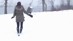 Beautiful woman walking in snowy park by water - stock footage