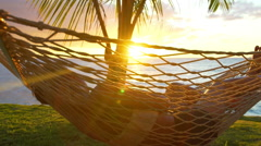 Romantic couple relaxing in tropical hammock at sunset. Summer Luxury Vacatio - stock footage
