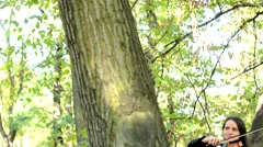 Young attractive happy woman plays on the violin by the big tree in the forest Stock Footage