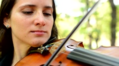 young attractive happy woman play on the violin in the park - concentrate - stock footage