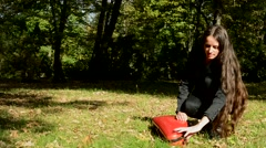 Stock Video Footage of young attractive happy woman sits in the park she withdraw violin from cover