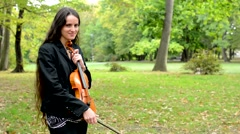 Young attractive happy woman hug the violin in the forest and fondle it Stock Footage