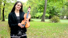 Young attractive absolutely happy woman hold a violin and flaunt - satisfied  Stock Footage