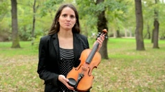 Young happy attractive woman describe parts of violin in the forest - she point  Stock Footage