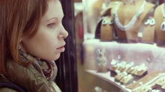 SLOW MOTION: young woman looks at the jewelry shop window. Shopping concept. Stock Footage